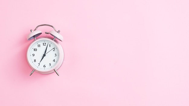 Top view vintage clock with pink background