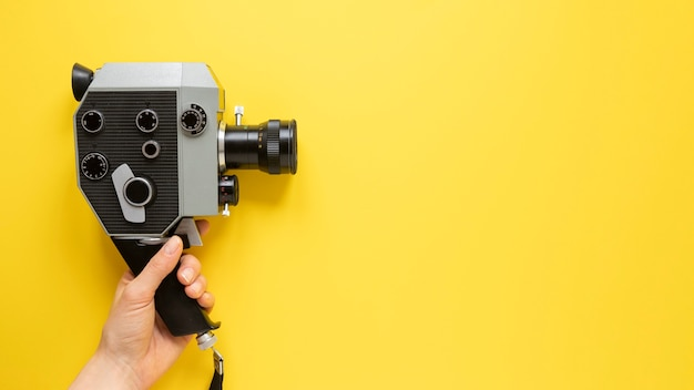 Top view vintage movie camera on yellow background with copy space