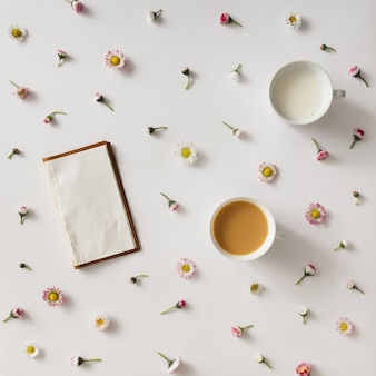 Top view of vintage notebook on white surface with colorful flowers and cup of coffee and milk