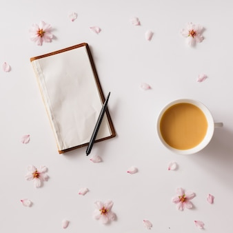 Top view of vintage notebook on white surface with pink flowers and cup of coffee or tea