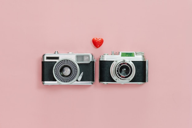 Top view of vintage old camera and little red heart on pink pastel background.