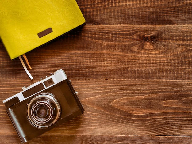 Top view vintage old camera and notebook on wooden background