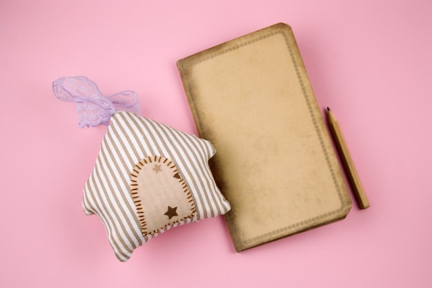 Top view vintage old paper,pencil and stuffed toy house on a pastel pink background