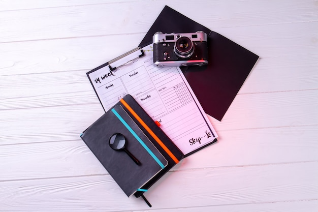 Top view vintage photo camera with clipboard and copybook. white desk background.