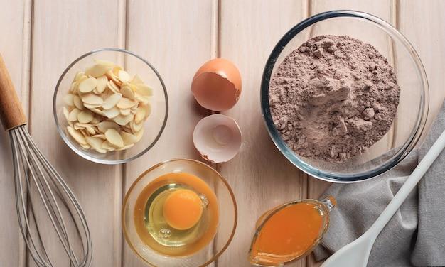ベーキングケーキの材料(卵、小麦粉、バター、アーモンド、砂糖)、ベーキング泡立て器とヘラが周りにある上面図ヴィンテージウッドキッチンテーブル。