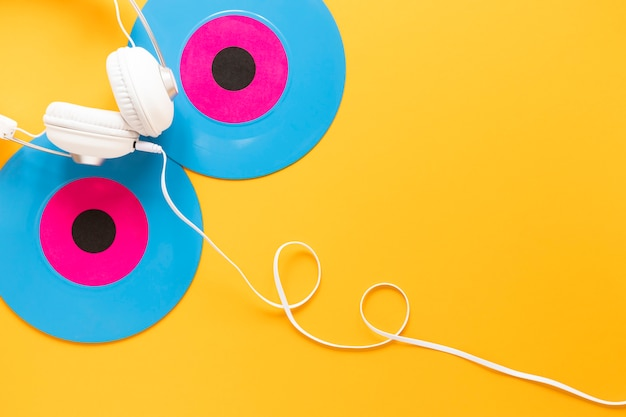 Top view of vinyl disc and earphones on yellow background