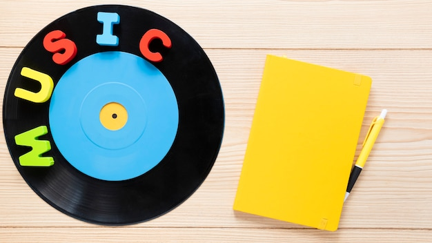 Top view of vinyl disc and notebook on wooden background