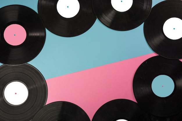 Top view of vinyl records border on dual background