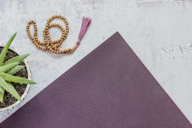 Top view of a violet yoga mat, bad wooden beads on white background. essential accessories for practice yoga and meditation. copy space