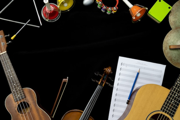 Top view of violin guitar and ukulele with percussion instruments on the black background