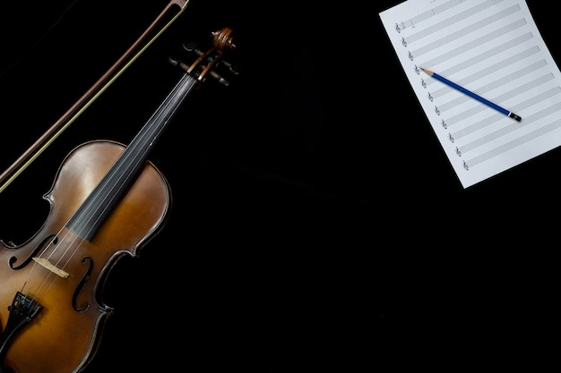 Top view of violin and musical note sheet on the black background