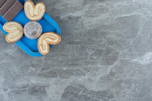 Vista dall'alto di wafer e biscotti sul piatto di legno blu.