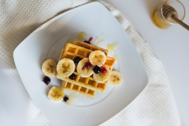 Top view of waffers with fruits on plate