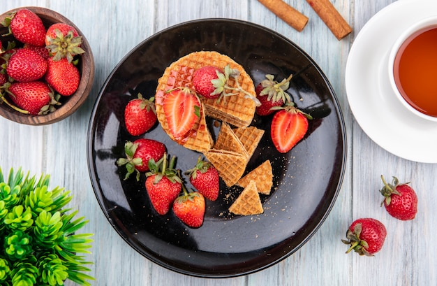 Top view of waffle biscuits with strawberries in plate and cinnamon cup of tea on wooden surface