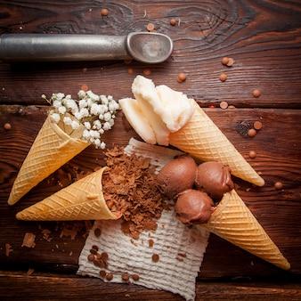 Coni di cialda vista dall'alto con gelato al cioccolato e gelato alla vaniglia e gocce di cioccolato e cucchiaio di gelato in tovaglioli di straccio