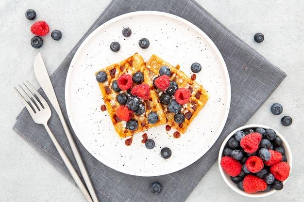 Вид сверху вафли на тарелке с лесными фруктами
