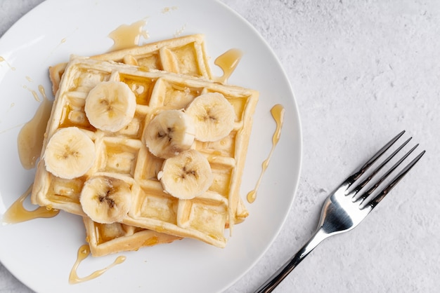 Top view of waffle with banana slices and honey