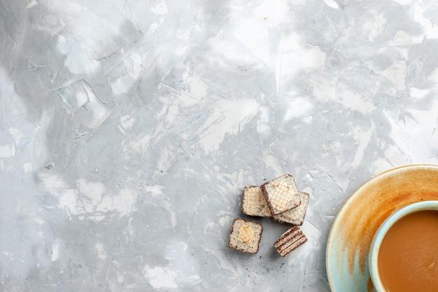 明るい白い背景の上のビューワッフルとコーヒーは甘い砂糖色を飲みます