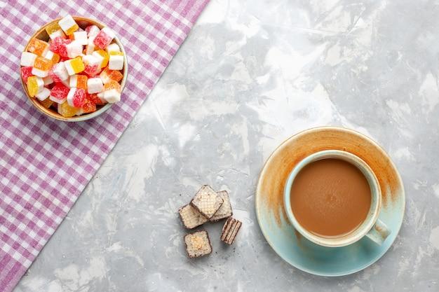 Вид сверху вафли и кофе с конфетами на светлом белом фоне напиток сладкого цвета сахара