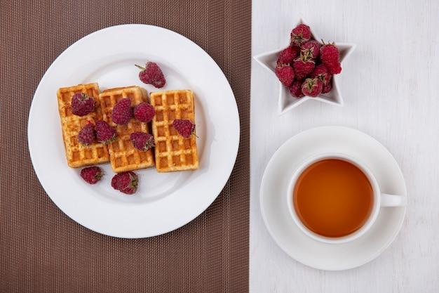 Вид сверху вафли на тарелке с малиной и чашкой чая на белом столе