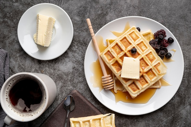Top view of waffles on plate with butter and cup of tea