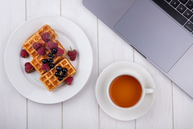 Top view waffles on a plate with raspberries and a cup of tea with a laptop on a white table