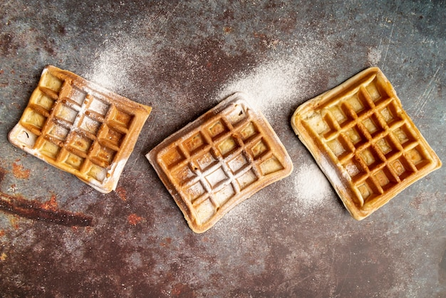 Top view of waffles on rusty surface covered in powdered sugar