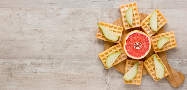 Top view of waffles with citrus and pears