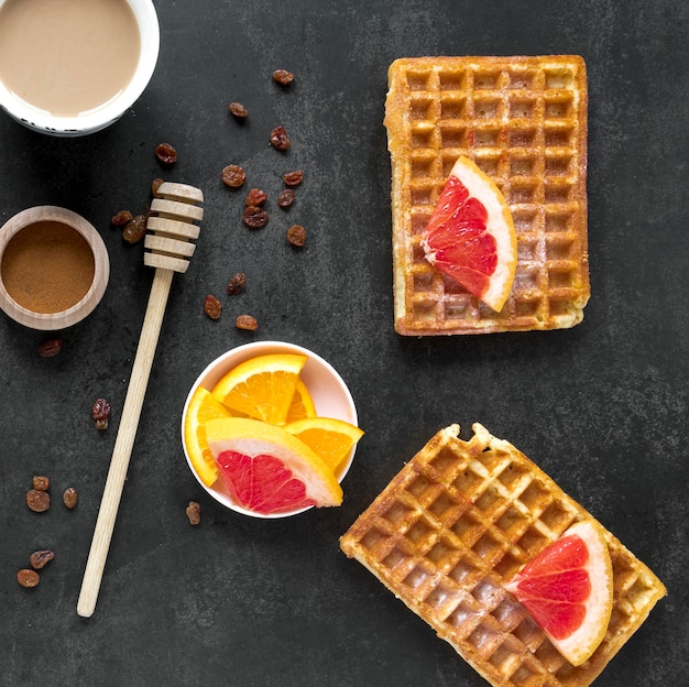 Top view of waffles with honey dipper and citrus