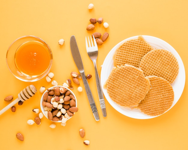 Top view waffles with honey and mix of nuts