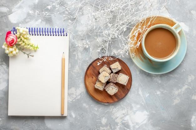 灰色がかった白い机の上のメモ帳とミルクコーヒーとトップビューワッフルチョコレートクッキードリンクコーヒー