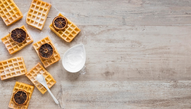 Top view of waffles with powdered sugar and dried citrus