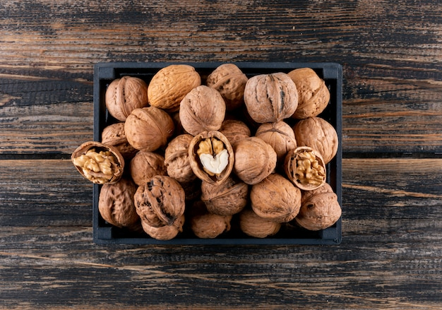Top view walnuts in black box on wooden  horizontal