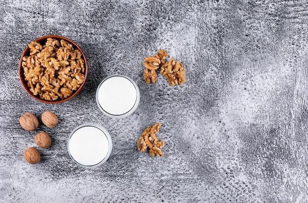 Noci di vista superiore in ciotola e bicchieri di latte sull'orizzontale di pietra