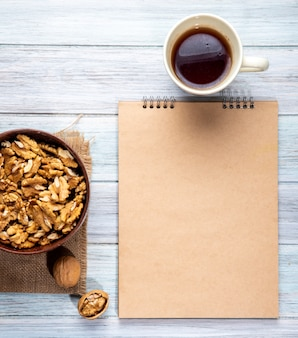Top view of walnuts in a bowl sketchbook and a mug with tea on a wooden