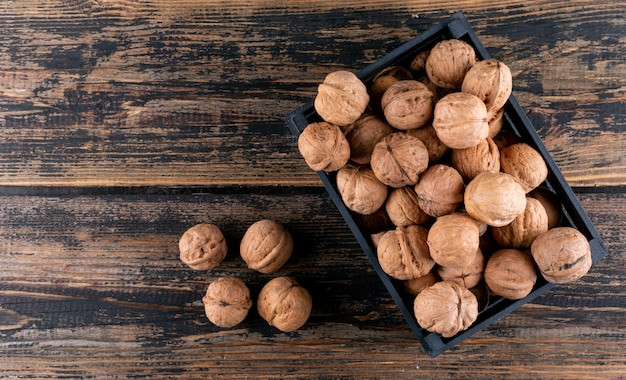 Top view walnuts in box on wooden  with copy space horizontal