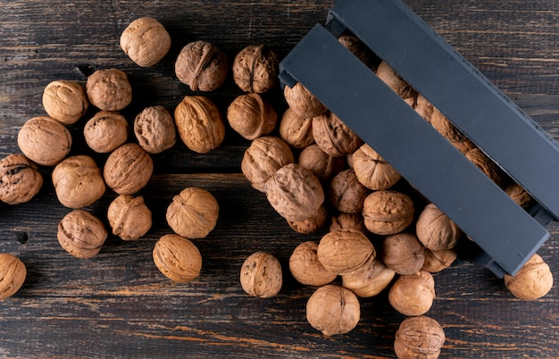 Top view walnuts from black box on wooden  horizontal