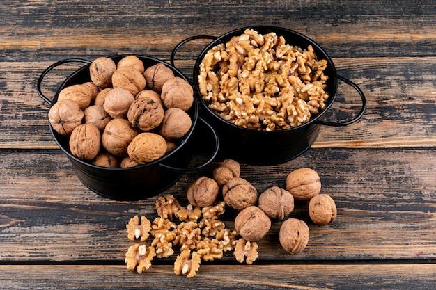 Вид сверху грецкие орехи в корзинах на деревянной горизонтали