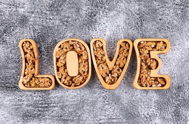 Вид сверху на грецкие орехи в форме любовных тарелок на камне горизонтальном