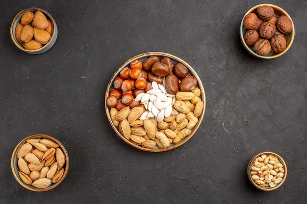 Top view of walnuts, peanuts, and other nuts on dark surface