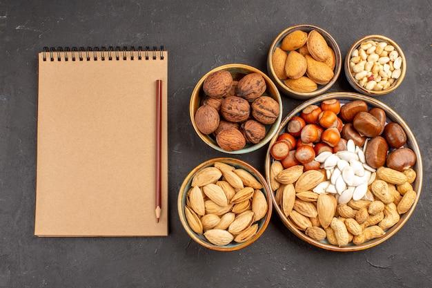 Vista dall'alto di noci, arachidi e altri dadi sulla superficie scura