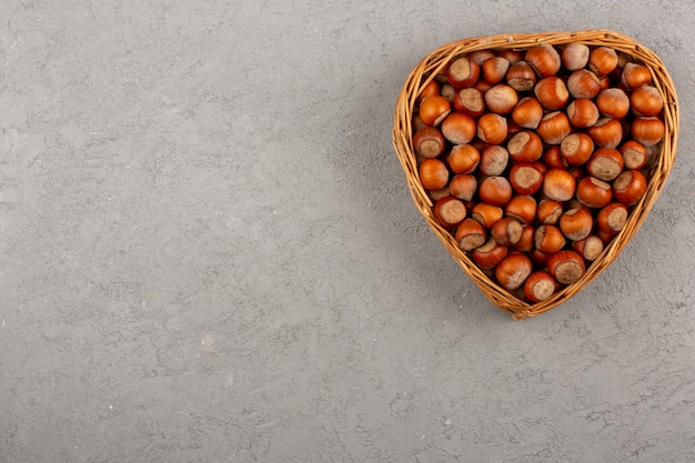 Вид сверху грецкие орехи в корзине на сером полу