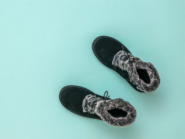 Top view of warm women's shoes with fur on a blue background. fashion stylish women's winter boots. flat lay.