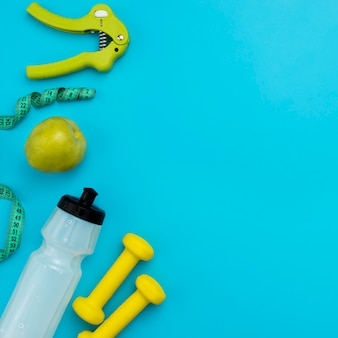 Top view of water bottle with measuring tape and apple