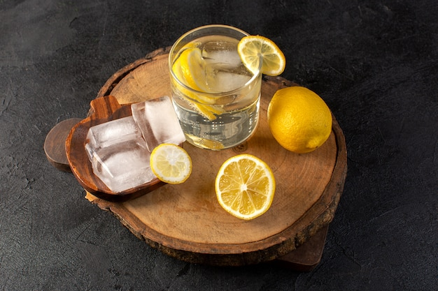 A top view water with lemon fresh cool drink inside glass with ice cubes with sliced lemons on the dark background cocktail drink fruit