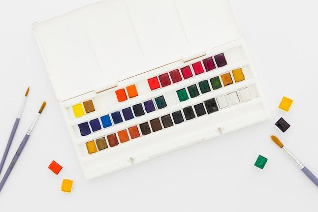 トップビューの水彩絵の具とペイントブラシ