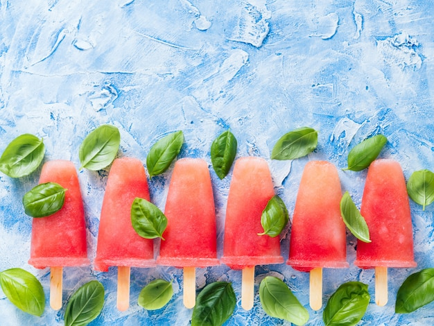 Top view of watermelon and basil popsicles with copy space