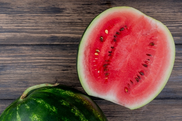 Top view of watermelon half with whole one on wooden background