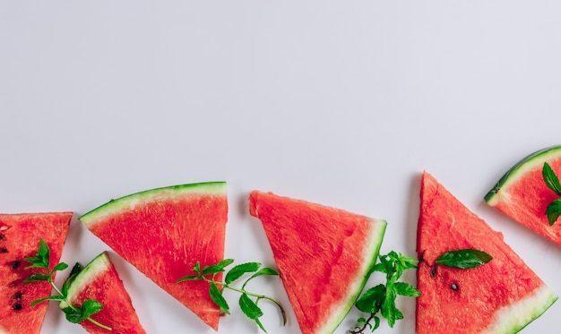 Top view of watermelon slices and mint leaves on white background. flat lay