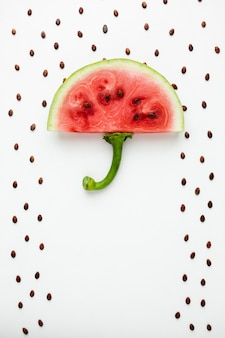 Top view watermelon umbrella with seeds on white background
